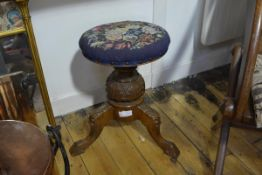A Victorian mahogany adjustable piano stool, the circular needlework seat on a leaf carved