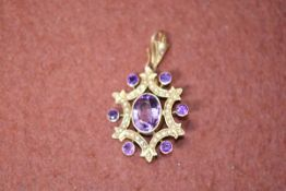 A 9ct gold Edwardian open work pendant set with an oval amethyst with rubover setting enclosed