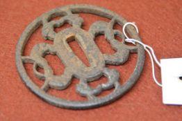A Japanese iron tsuba of sukashi type, pierced with zoomorphic designs. Diameter 8cm