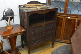 An Edwardian carved oak music cabinet, the top decorated with stylised foliage, the sides with