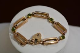 A 9ct gold over link rose gold bracelet with four peridot millegrain set spacers complete with heart