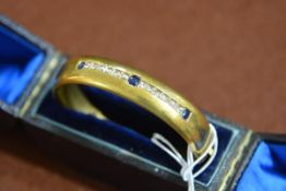 A late Victorian diamond and sapphire bangle, mounted in yellow metal (unmarked but probably