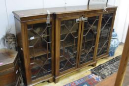 An early 20th century mahogany low breakfront bookcase, the moulded edge top above an arrangement of