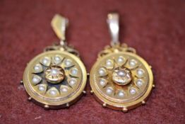 A pair of Victorian yellow metal pendant earrings with centre cluster of half pearls and inner