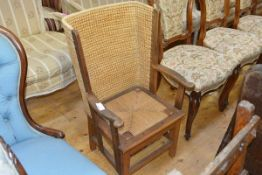 A child's oak-framed Orkney chair, the winged back above a drop in seat between outscrolled arms and