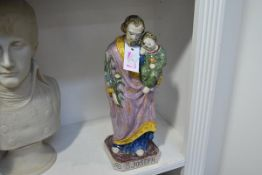 A Continental glazed earthenware figure of Saint Joseph, modelled standing and holding the Christ