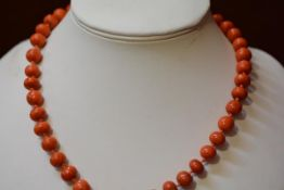 A pink coral graduated Chinese style bead necklace with yellow metal engraved clasp fastening with