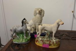 A group of three 19th century Staffordshire animal models comprising: a seated spaniel with puppies,