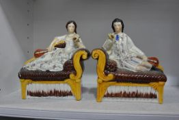 A pair of 19th century Staffordshire flatback figures of a lady and gentleman, each reclining on a