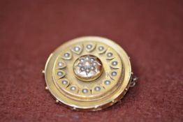 A Victorian yellow metal circular brooch with inset half seed pearl cluster, enclosed within a