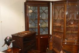 A George III mahogany standing corner cupboard, the upper section with moulded cornice above a