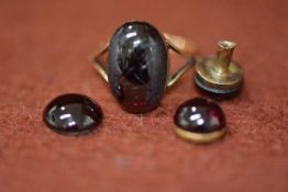 A 9ct gold garnet cabochon ring, and two yellow metal garnet mounted studs. Gross weight 7.36g (3)