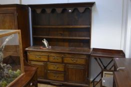 A small George III oak dresser and rack, the rack with moulded cornice above a scalloped apron,