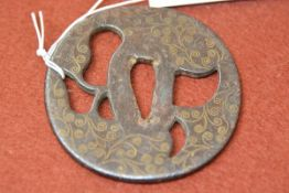 A Japanese iron tsuba, gilt-inlaid with scrollwork. 8cm