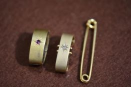 A 9ct gold safety pin style brooch and a 9ct gold hinged scarf ring with gypsy style set rose cut