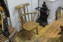 An early 19th century primitive elm Windsor armchair, the top rail above a spindle back, the