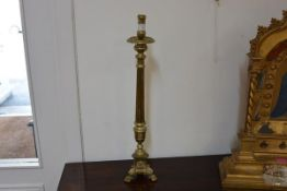 An ecclesiastical brass altar stick in 18th century style, with integral drip pan, fluted standard