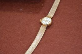 A lady's Omega 9ct gold wristwatch, the silvered dial with baton numerals, on a hallmarked