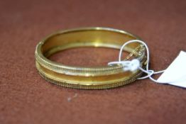 An Edwardian 15ct gold stiff hinged bangle with ropework border, complete with safety chain,