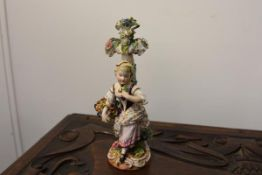 A Dresden porcelain figure of a girl carrying a basket of flowers, by a floral encrusted stump on