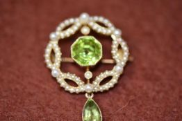An Edwardian 15ct gold openwork brooch, the centre octagonal peridot with surround of half