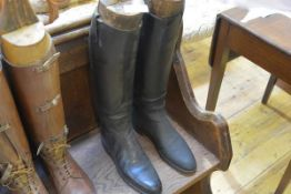 A pair of early 20th century black leather riding boots, in period wooden boot trees.