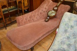 A Victorian chaise longue, with buttoned single scroll end and raised on turned legs moving on
