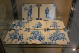 A group of eight 18th century Delft blue and white tiles, four depicting warriors on horseback,
