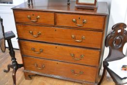 A George III mahogany chest of drawers, the rectangular top above two short and three long