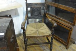 A carved oak open armchair in 17th century style, the backsplat carved with a stylised flowerhead
