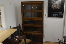An early 20th century oak sectional bookcase, with four sections over a base with glazed door. 180cm