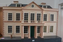 A large 20th century painted wooden doll's house, in the Georgian style, with columned porch beneath