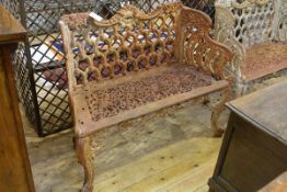 A cast iron two seater garden bench in the Coalbrookdale style, weathered, the back and seat cast