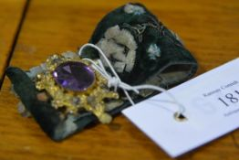 """A gilt-metal and embroidered velvet cuff, the 19th century clasp set with a large glass """"amethyst"""""""