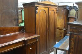 A Victorian mahogany press cupboard, with pedimented cornice above a pair of arched panel doors on a
