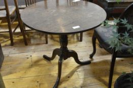 A George III oak tilt top tripod table, the circular top on a turned standard, with pointed pad