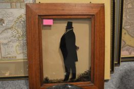 An English reverse painted on glass portrait silhouette of a gentleman in a top hat, c. 1830, in a