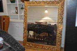 A large giltwood mirror in the Baroque taste, the rectangular bevelled plate within a frame