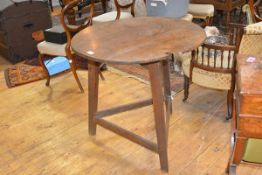 An early 19th century elm cricket table, the three plank top above a scroll carved apron and