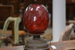 A 1ate 19th century brass oil lamp with a large dimpled ruby glass shade. Shade height 26cm