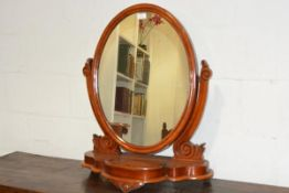 A Victorian mahogany toilet mirror, the oval plate within a conforming frame swinging between scroll