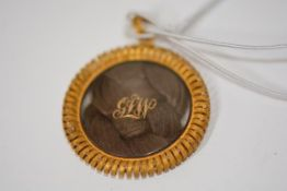 A Regency gold hair locket, circular, the double sided glass enclosing plaited hair mounted with a