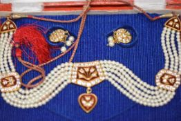 An Indian cultured pearl, paste, enamel and silk cord necklet, mounted in yellow metal, the