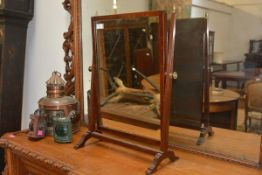 A George III mahogany swing toilet mirror, the rectangular plate within a frame decorated with