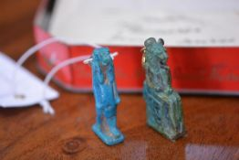 Two Egyptian turquoise faience amulets, one of a seated lion-headed goddess, the other a standing