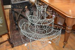A 19th century painted wrought-iron demilune three-tier plant stand, the radiating shelves with