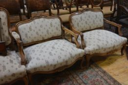 A pair of Louis XV style walnut framed love seats, c. 1900, each with leaf and scroll-carved crest