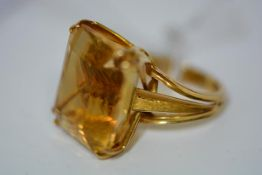 A striking large citrine dress ring, the emerald-cut stone claw-set on split shoulders, the yellow