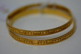 A pair of Indian yellow metal bangles, unmarked but test as 22ct gold, each decorated with star