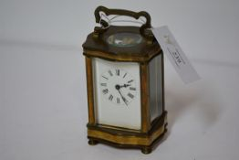 A French brass-cased carriage clock, c. 1900, of characteristic form, the white enamel dial with